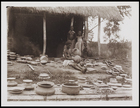 1 female and 2 children standing among a large collection of pots