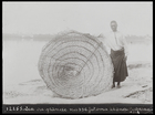 man standing by large wicker fishing trap