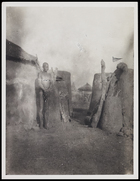 Female standing among huts in compound