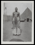 the chief of Mokunji wearing a leapoard skin around his waist, standing in front of large conical hut