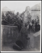 Elderly female wearing necklace, bracelets and loin cloth, standing smoking a pipe beside an ancestral shrine with a large group of people in the background in a compound