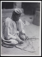 1 male dressed in a tunic and head scarf plaiting fibres