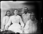 Mrs. Dauncey siting in chair with two women and a man, all South Seas teachers of the London Missionary Society, all wearing European clothing, against woven mat backdrop