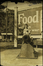 Photograph of a boy sitting on a cannon in front of a 'Food will win the war' billboard, Memphis, TN
