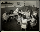 Young blind / visually impared children with a female teacher in the nursery at the New York Association for the Blind, 111 East 59th Street, New York, 1933 (silver gelatin print)