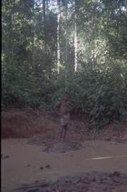 A youth wearing shorts standing on a raised mud bank at the edge of a muddy river or water hole in the forest.