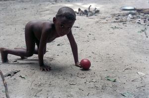Close-up of a child crouching on all fours with a round red fruit on the ground just in front of him or her.