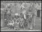 chief Ebanja (?) seated with two women, with four men standing behind holding spears- two with painted faces