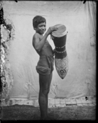 Boy holding large elaborately carved drum, standing in front of white cloth backdrop