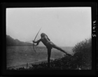 man balancing on one leg in the act of firing an arrow