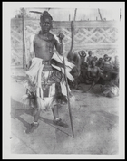 bambi of Mushenge holding wooden staff, seated crowd in the background (and palace walls ?)
