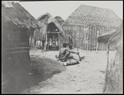 woman and children among huts, one hut under construction