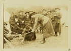 Photograph of Women in Uniform Hammering a Tent Stake